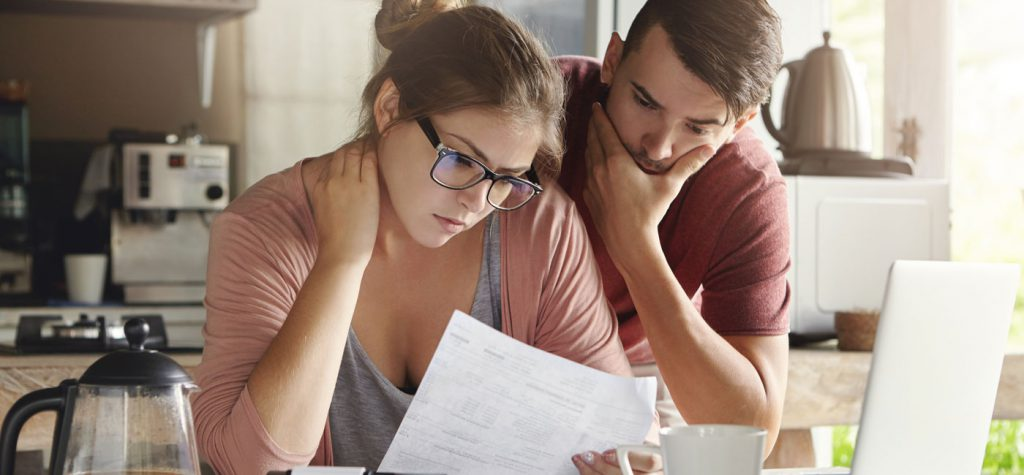 Couple Looking At Debt Claims Documents.